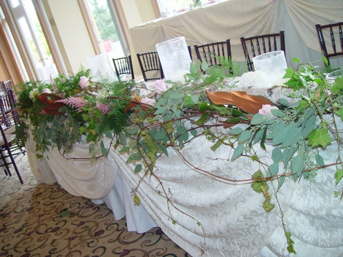 Rustic Headtable design based on long birch logs, grapevine, flowers, foliage, candles.