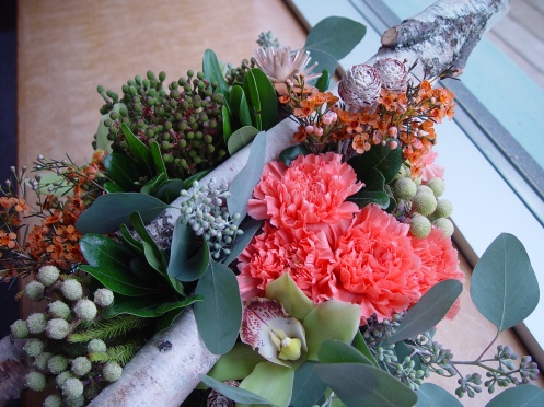 Rustic centrepiece with birch logs, moss, pods, cones, flowers.